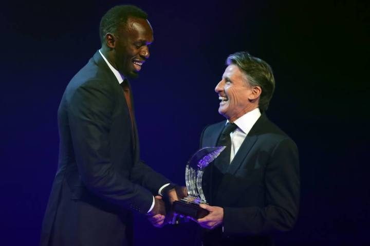 Jamaican athlete Usain Bolt (L) shakes hands with IAAF President Sebastian Coe after being awarded 2016 male world athlete of the year in Monaco on December 2, 2016 during the International Association of Athletics Federations (IAAF) gala. / AFP PHOTO / VALERY HACHE
